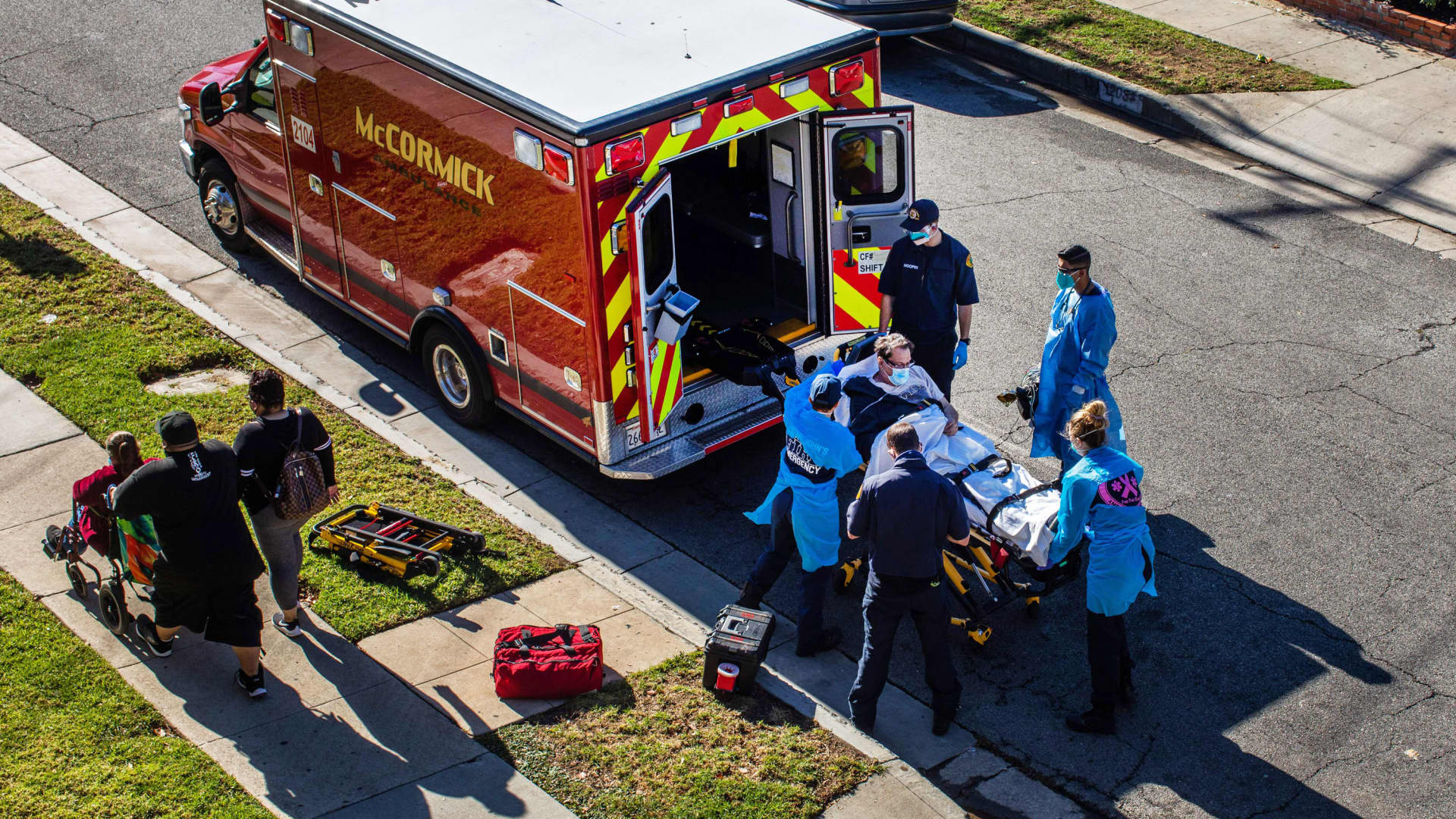 After administering him with oxygen, County of Los Angeles paramedics load a potential Covid-19 patient in the ambulance before transporting him to a hospital in Hawthorne, California on December 29, 2020 as a family walks by.