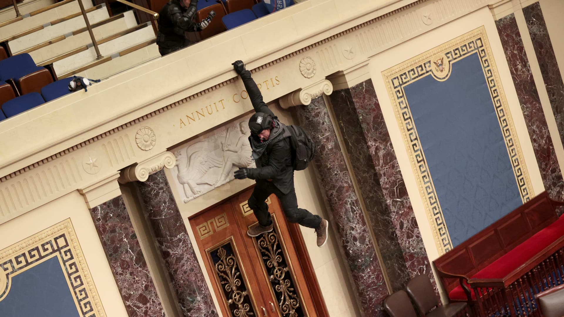 A protester dangled from the balcony in the Senate Chamber on January 6, 2021, in Washington.