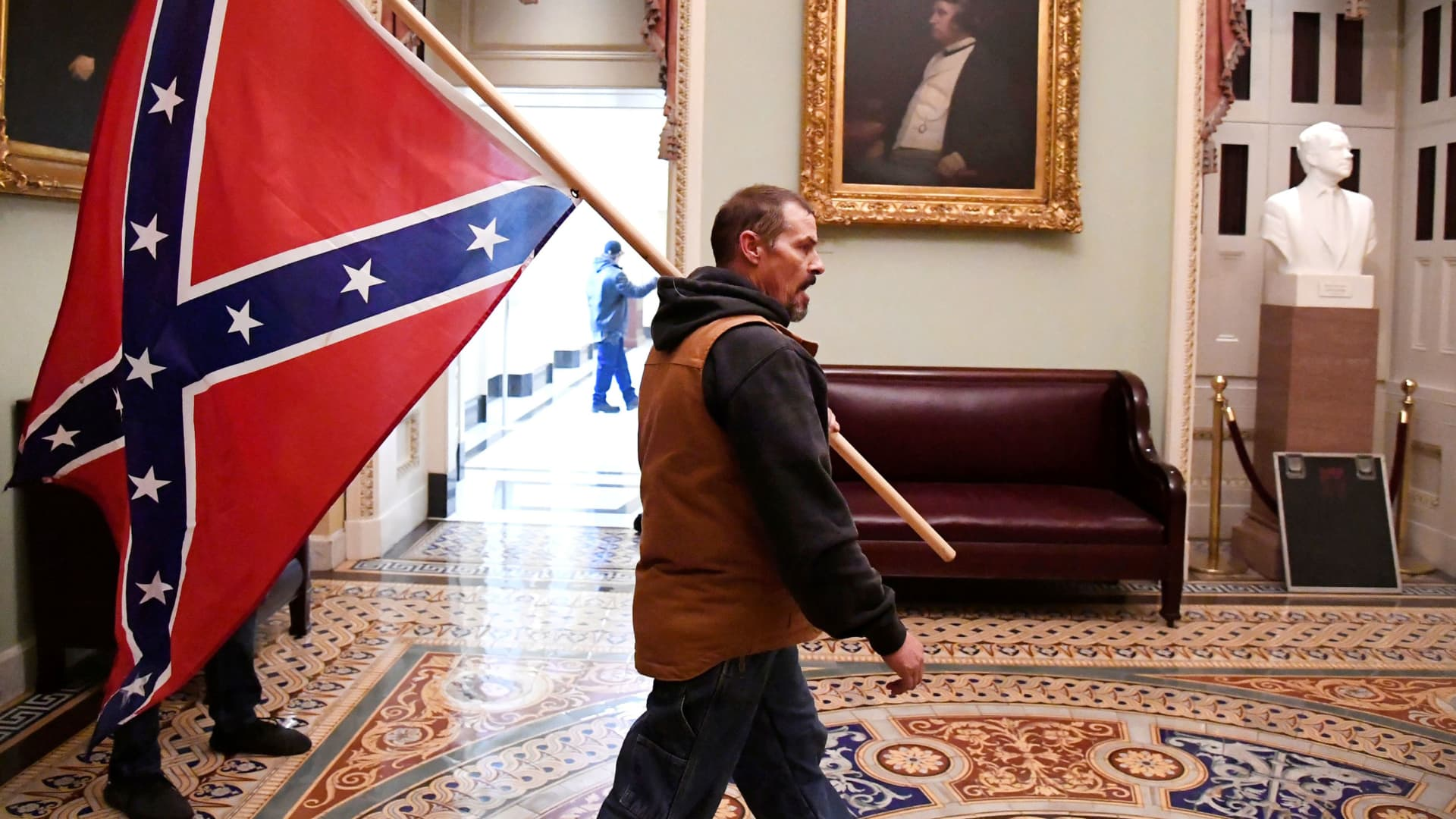 A supporter of President Donald Trump carries a Conferderate battle flag on the second floor of the U.S. Capitol near the entrance to the Senate after breaching security defenses, in Washington, January 6, 2021.