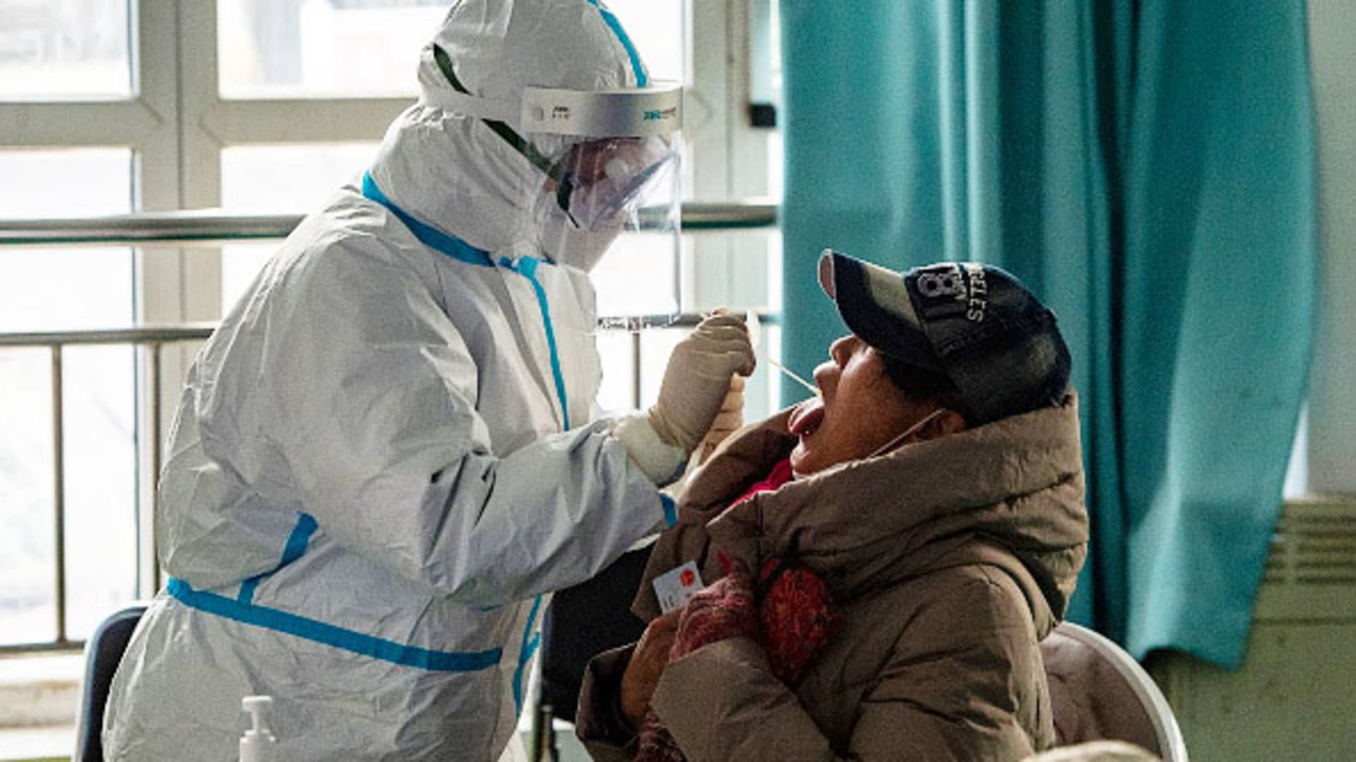 A medical worker wearing a protective suit collects a throat swab from a local resident for Covid-19 antigen rapid test at a temporary testing center on Jan. 6, 2021 in Shijiazhuang, Hebei Province of China.