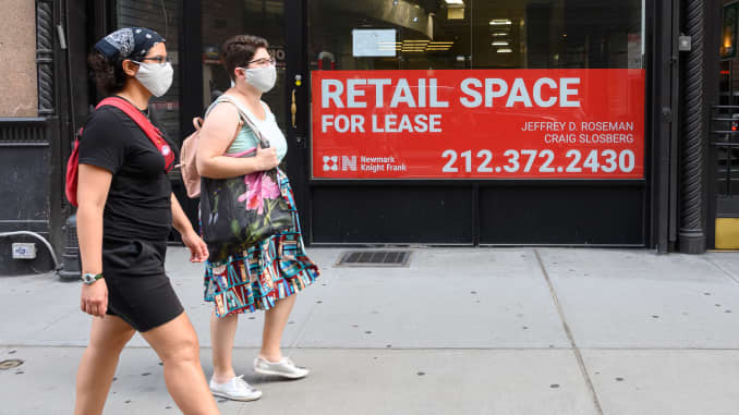 People walk by a sign displayed outside a retail space for lease as the city continues Phase 4 of re-opening following restrictions imposed to slow the spread of coronavirus on August 26, 2020 in New York City.