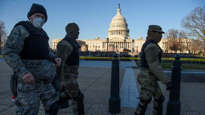 Các thành viên của Lực lượng Vệ binh Quốc gia DC đi ngang qua Tòa nhà Quốc hội Hoa Kỳ ở thủ đô Washington vào ngày 7 tháng 1 năm 2020, một ngày sau khi những người ủng hộ Tổng thống sắp mãn nhiệm Donald Trump xông vào tòa nhà.