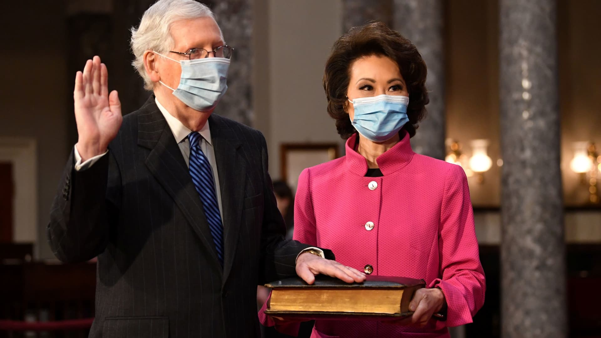 Senate Majority Leader Mitch McConnell (R-KY) participates in a swearing-in ceremony for the 117th Congress with Vice President Mike Pence, as his wife, Transportation Secretary Elaine Chao, holds the Bible in the Old Senate Chambers at the U.S. Capitol Building in Washington, DC, January 3, 2021.