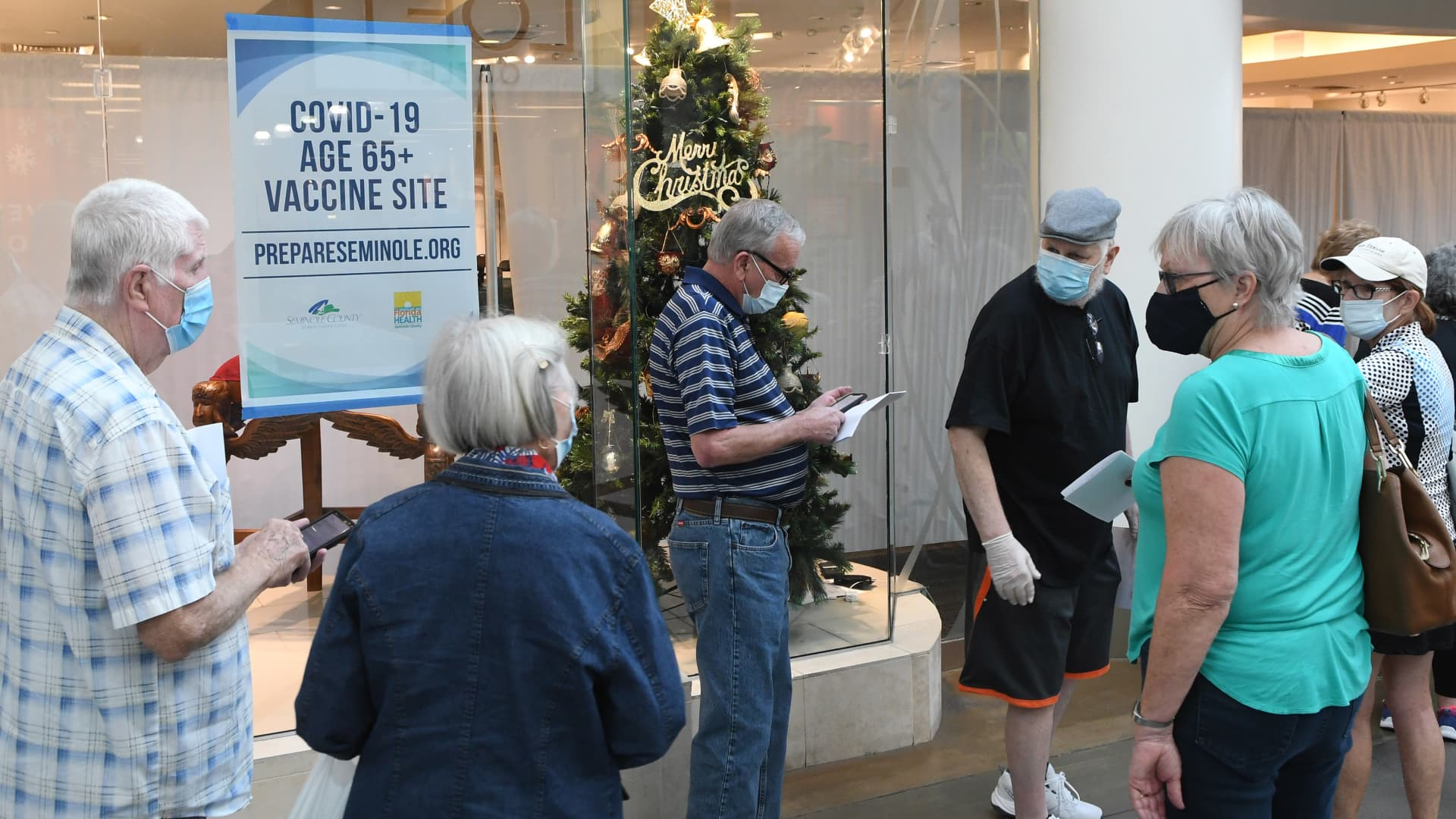 People wait in a line on New Year's Eve to receive a COVID-19 vaccination at a site for seniors in an unoccupied store at the Oviedo Mall. Governor Ron DeSantis ordered that Florida residents 65 and older be included in the first group to be offered coronavirus vaccinations, against the federal CDC recommendations.
