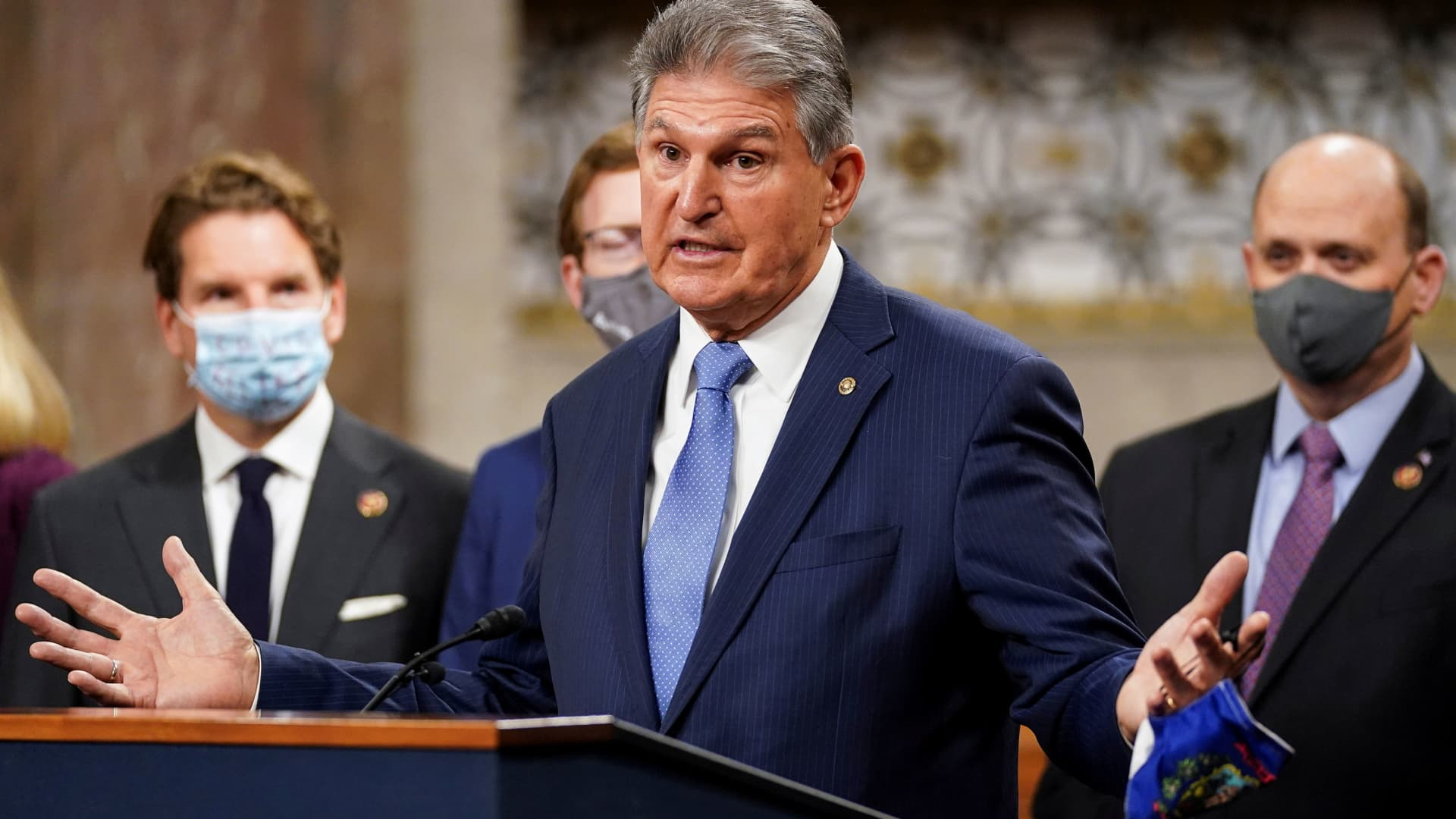 Senator Joe Manchin (D-WVA) removes his mask to speak as bipartisan members of the Senate and House gather to announce a framework for fresh coronavirus disease (COVID-19) relief legislation at a news conference on Capitol Hill in Washington, December 1, 2020.