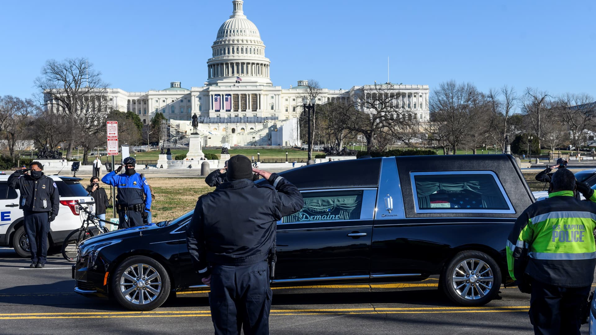 US Capital police stand at attention as the casket with fallen police officer, Brian Sicknick, passes during a funeral procession in Washington, DC on January 10, 2021.