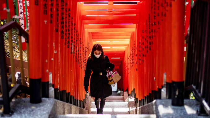 A woman wearing a face mask walks under a row of gates at Hie Shrine in Tokyo on January 7, 2021.
