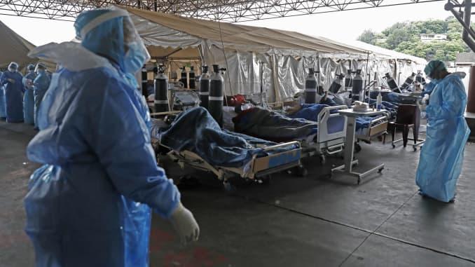 Petugas perawatan kesehatan profesional yang mengenakan alat pelindung diri (APD) masuk ke bangsal sementara yang didedikasikan untuk pengobatan kemungkinan pasien virus corona COVID-19 di Rumah Sakit Akademik Steve Biko di Pretoria pada 11 Januari 2021.
