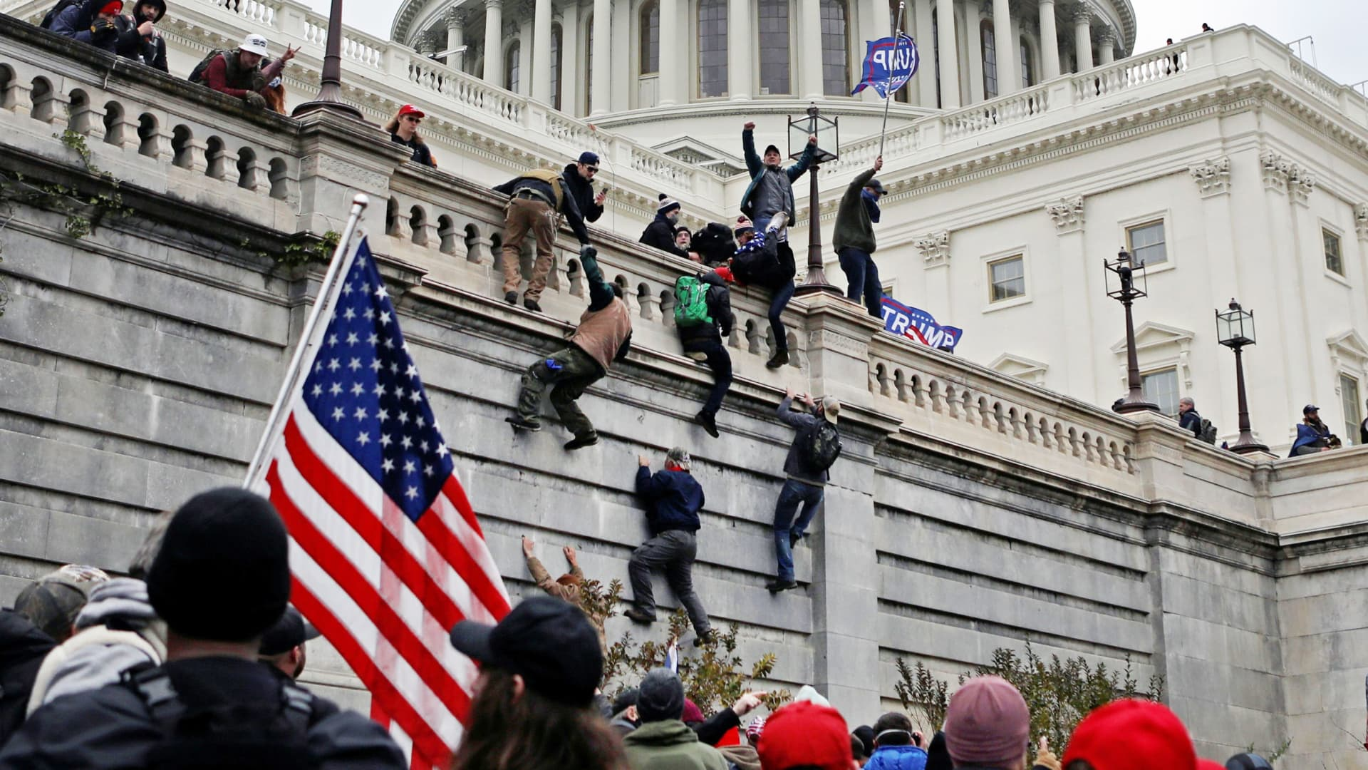Supporters of U.S. President Donald Trump climb a wall during a protest against the certification of the 2020 presidential election results by the Congress, at the Capitol in Washington, January 6, 2021.