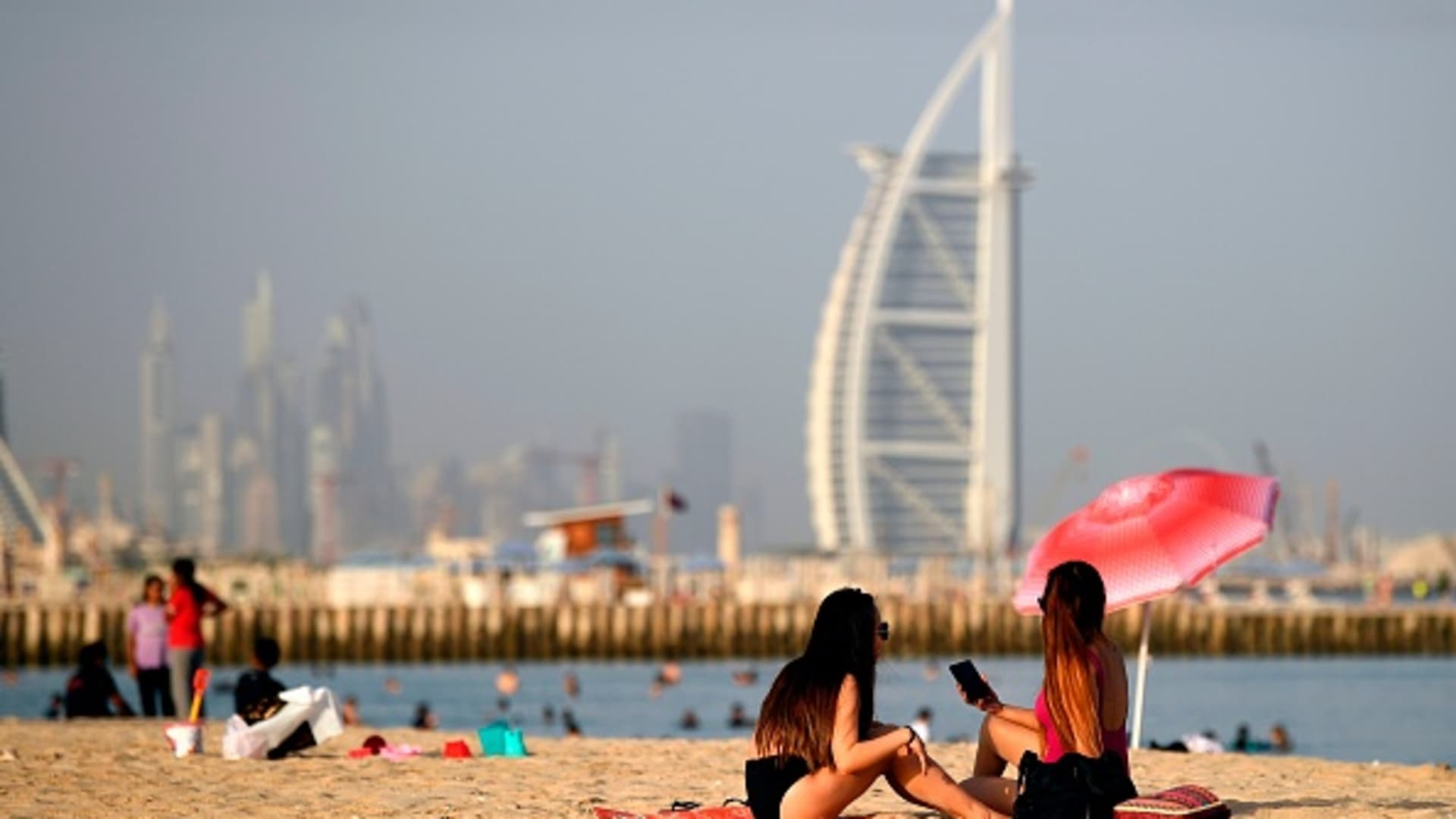 Woman sunbathers sit along a beach in the Gulf emirate of Dubai on July 24, 2020, while behind is seen the Burj al-Arab hotel.