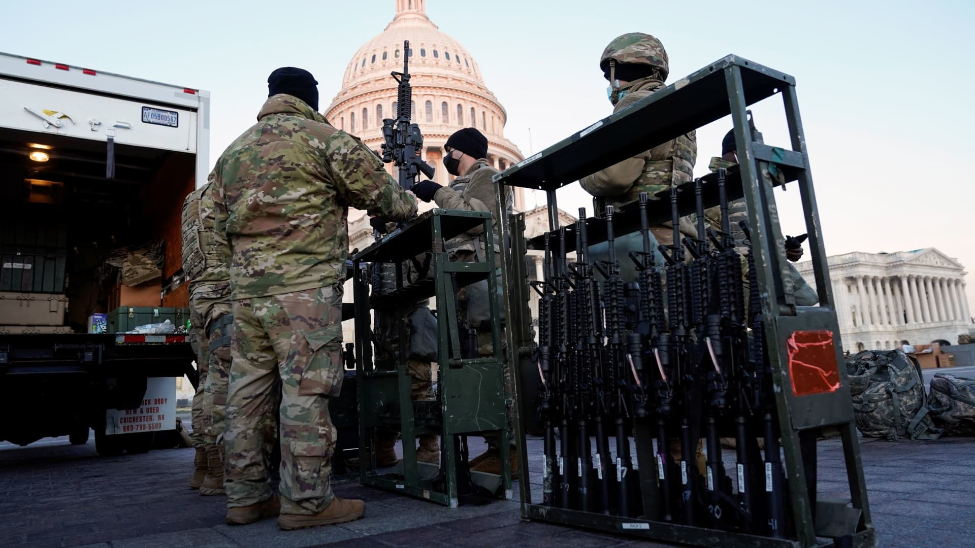 Members of the National Guard are given weapons before Democrats begin debating one article of impeachment against U.S. President Donald Trump at the U.S. Capitol, in Washington, U.S., January 13, 2021.