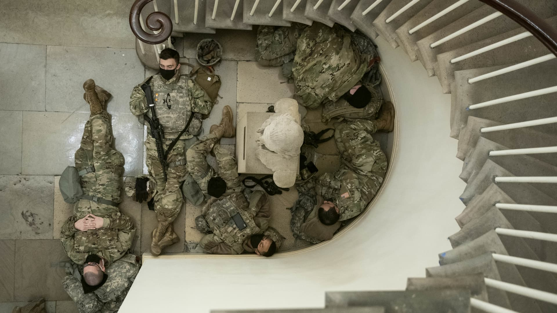 Members of the National Guard rest in a hallway of the U.S. Capitol building in Washington, D.C., U.S., on Wednesday, Jan. 13, 2021.