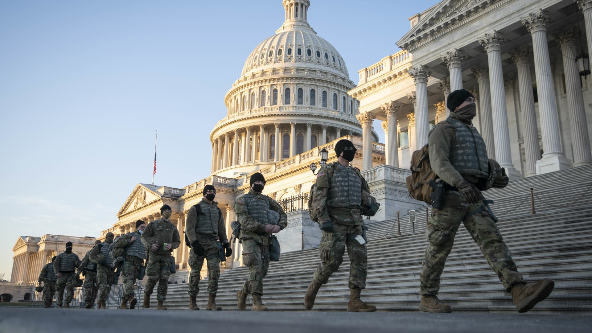 Members of the National Guard walk outside of the U.S. Capitol building in Washington, D.C., U.S., on Wednesday, Jan. 13, 2021.