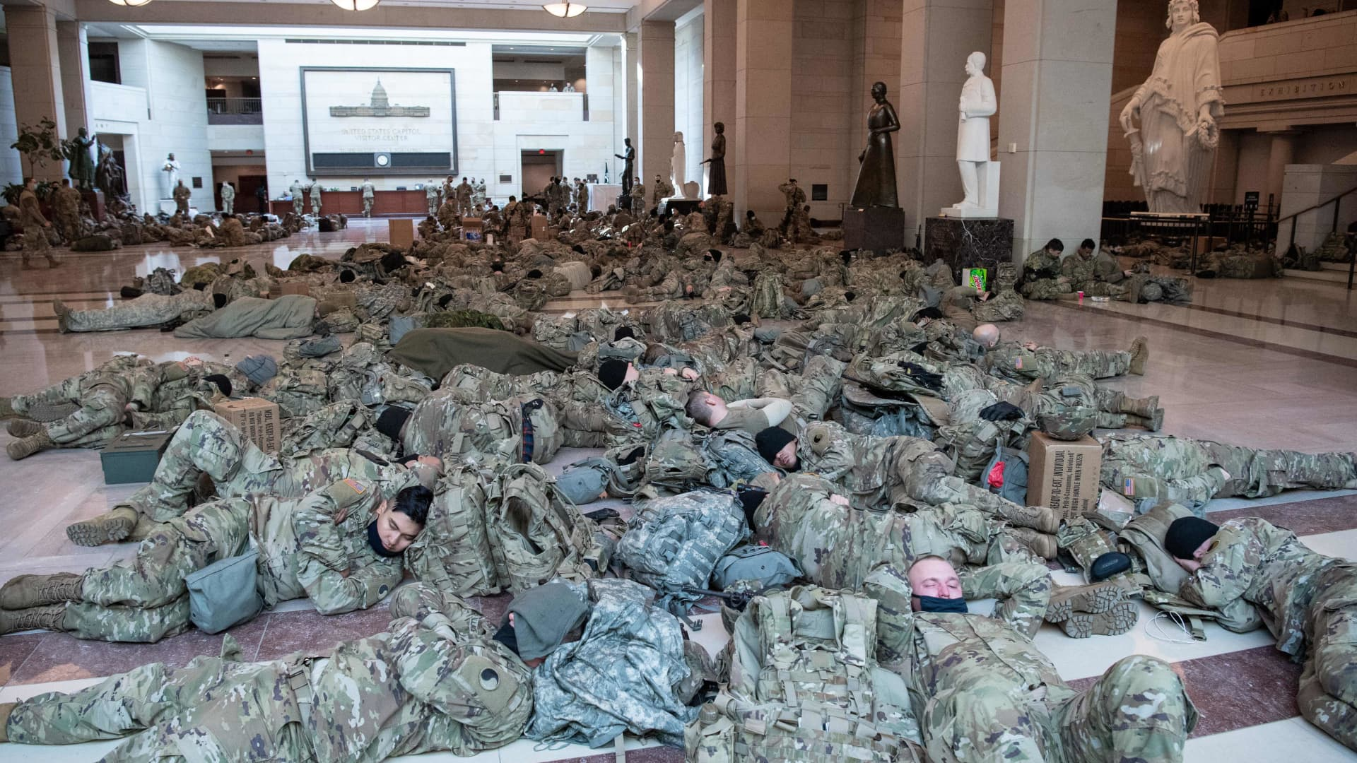 Members of the National Guard rest in the Capitol Visitors Center on Capitol Hill in Washington, DC, January 13, 2021, ahead of an expected House vote impeaching US President Donald Trump.
