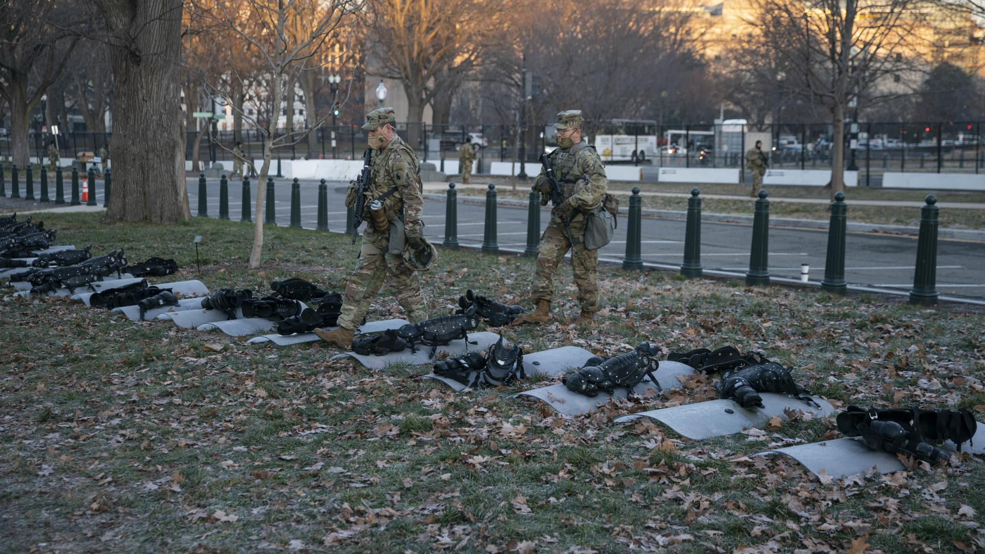 Members of the National Guard stand in front of riot shields and body armor on the lawn of the U.S. Capitol in Washington, D.C., U.S., on Wednesday, Jan. 13, 2021.