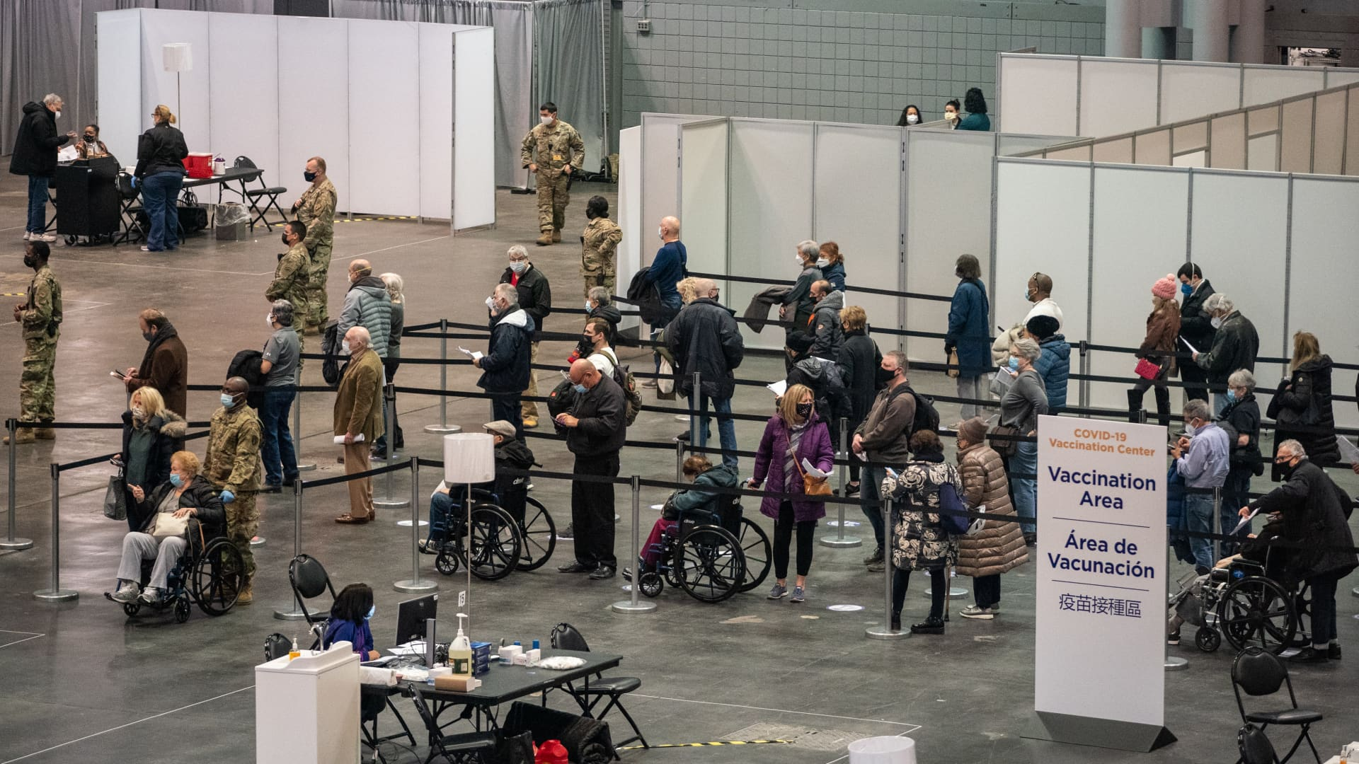 People stand in line to receive a dose of the Covid-19 vaccination at the Jacob Javits Convention Center in New York, U.S., on Wednesday, Jan. 13, 2021.