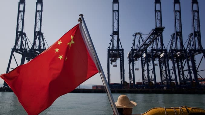 Một lá cờ Trung Quốc gắn sau thuyền bay trong gió khi các container hàng hóa đậu trên bến cảng Thâm Quyến ở Thâm Quyến, Trung Quốc.