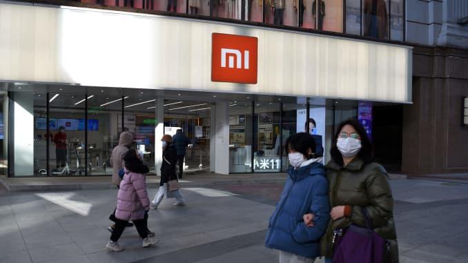 Mọi người đi ngang qua một cửa hàng Xiaomi ở Bắc Kinh vào ngày 15 tháng 1 năm 2021, khi cổ phiếu của công ty này sụp đổ vào ngày 15 tháng 1 sau khi Hoa Kỳ đưa gã khổng lồ điện thoại thông minh và một loạt các công ty Trung Quốc khác vào danh sách đen.