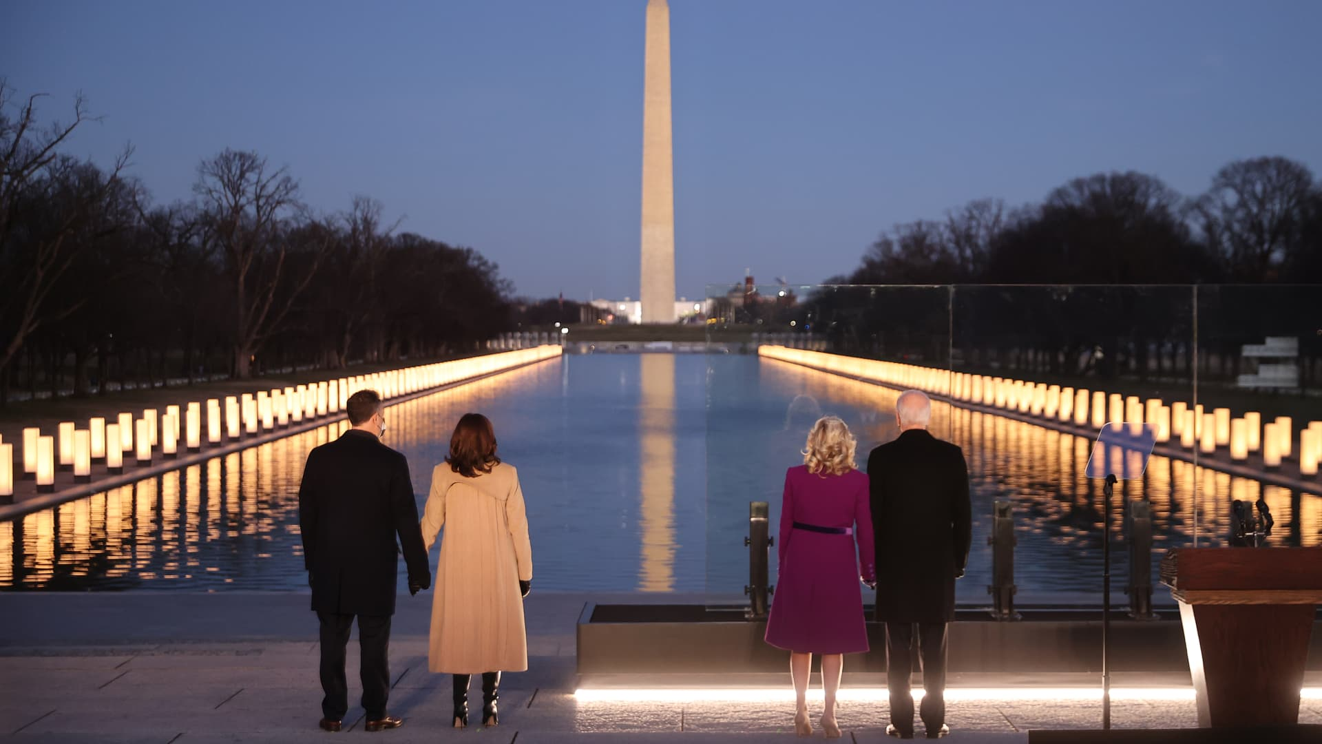 (L-R) Douglas Emhoff, U.S. Vice President-elect Kamala Harris, Dr. Jill Biden and U.S. President-elect Joe Biden look down the National Mall as lamps are lit to honor the nearly 400,000 American victims of the coronavirus pandemic at the Lincoln Memorial Reflecting Pool January 19, 2021 in Washington, DC.