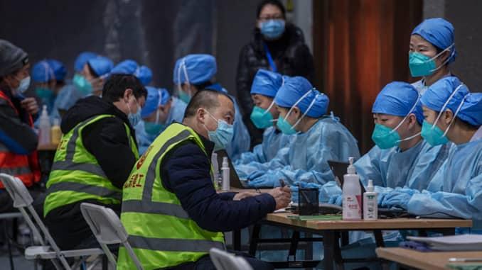 Pekerja perawatan kesehatan dan sukarelawan Tiongkok mengenakan pakaian pelindung saat mereka mendaftarkan orang untuk menerima suntikan vaksin Covid-19 di pusat vaksinasi massal untuk Distrik Chaoyang pada 15 Januari 2021 di Beijing, Tiongkok.