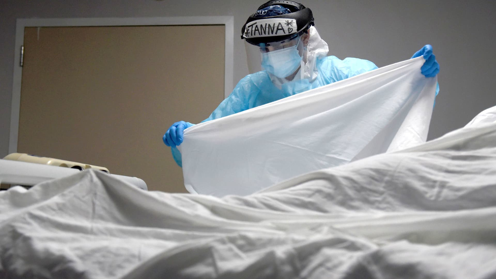 Tanna Ingraham places a sheet over the body of a patient who died inside the coronavirus disease (COVID-19) unit at United Memorial Medical Center in Houston, Texas, December 30, 2020.