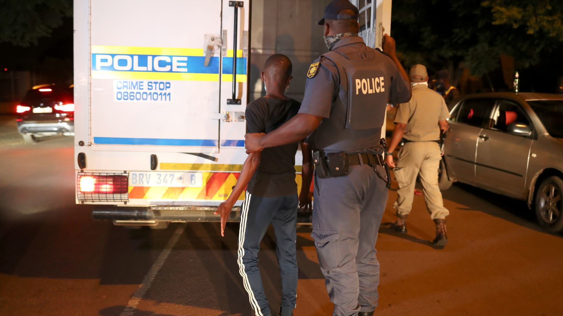 A police officer detains a man during a patrol as a nighttime curfew is reimposed amid a nationwide coronavirus disease (COVID-19) lockdown, in Pretoria, South Africa, January 9, 2021.