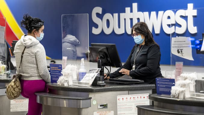 A traveler wearing a protective mask speaks with an attendant at the Southwest Airlines check-in area at Oakland International Airport in Oakland, California, U.S., on Tuesday, Jan. 19, 2021.