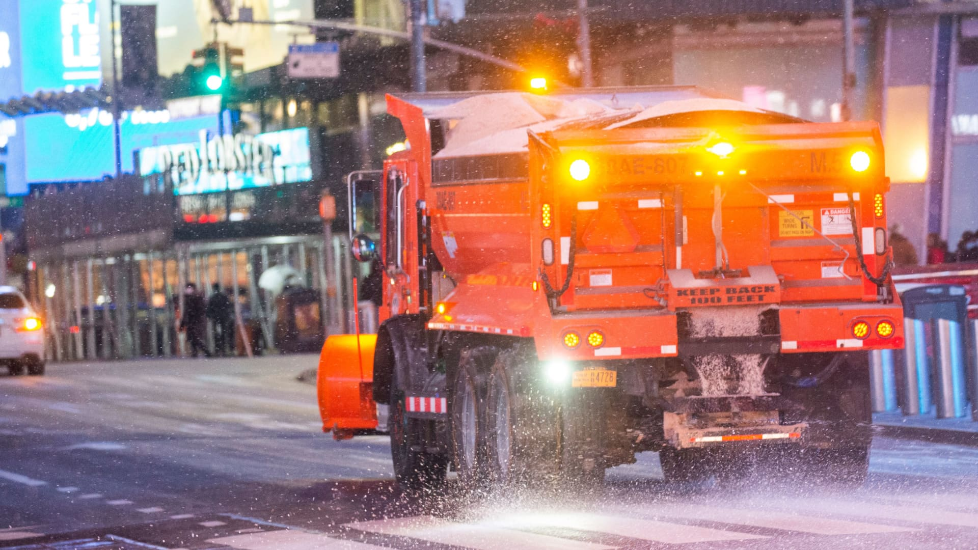 A truck spreads salt as snow falls during a winter storm in Times Square on January 31, 2021.