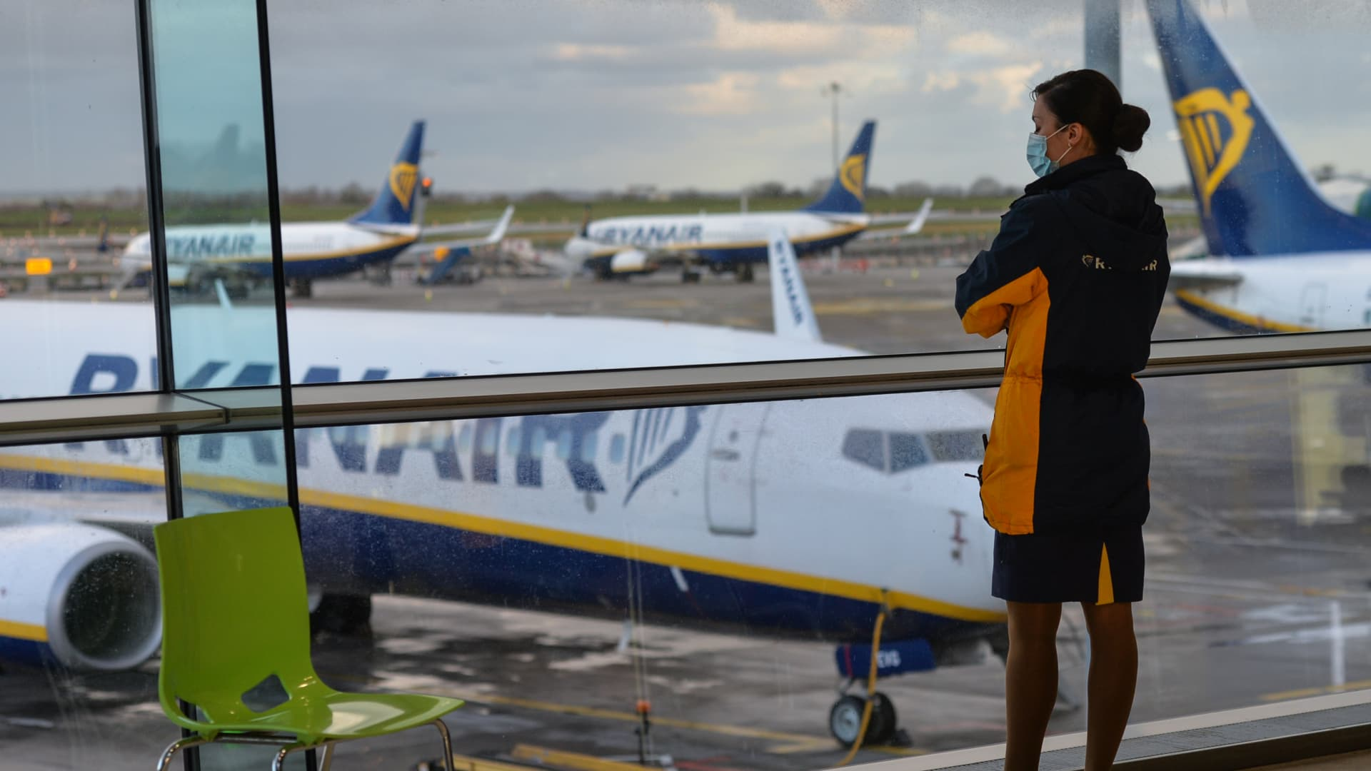 A member of Ryanair cabin crew looks out of the window at Ryanair planes.