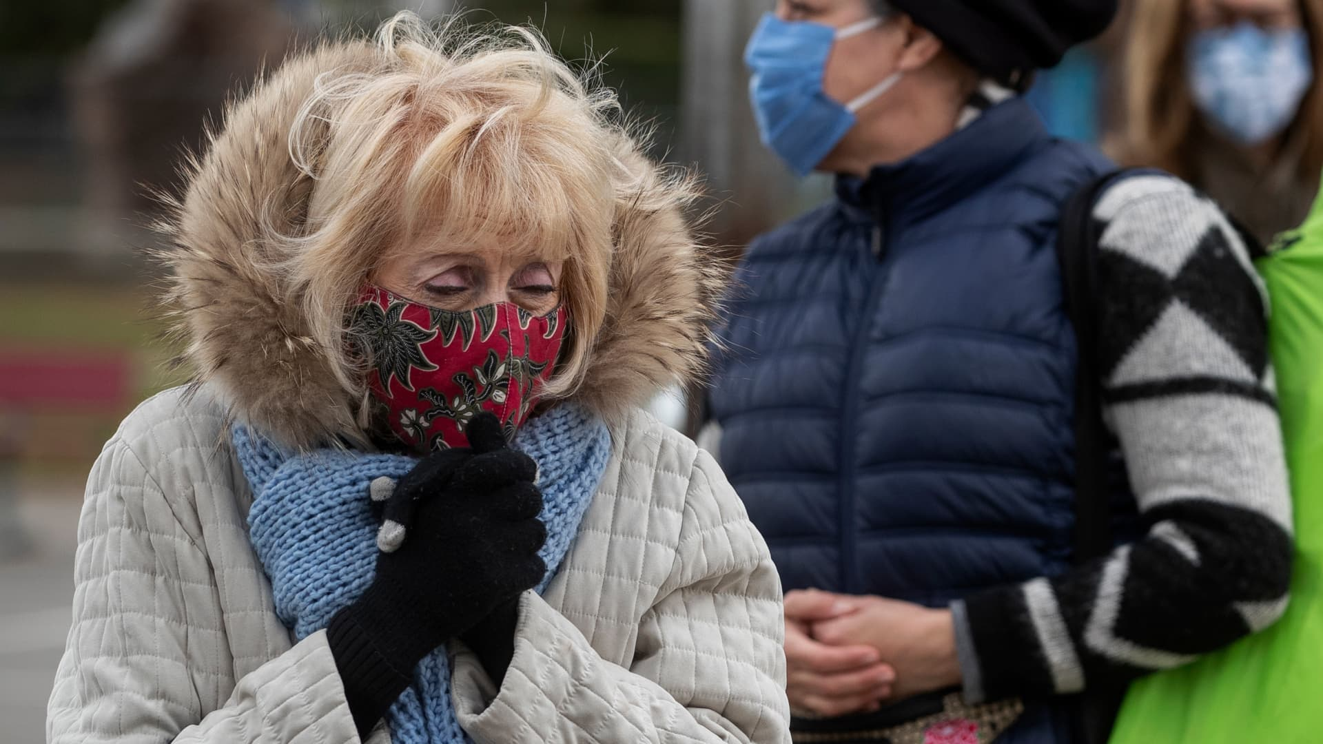 Evelyn Mellman, 82, of Studio City, tries to keep warm while waiting with others in the by appointment only line to get vaccine shots to protect against the coronavirus at the Balboa Sports Complex in Encino.