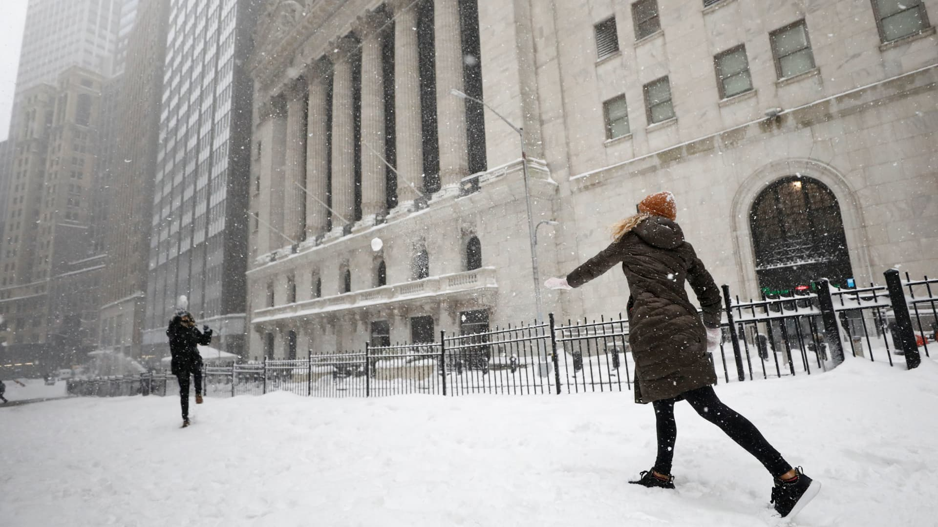 People have a snowball fight outside the New York Stock Exchange (NYSE) during a snow storm in New York, February 1, 2021.