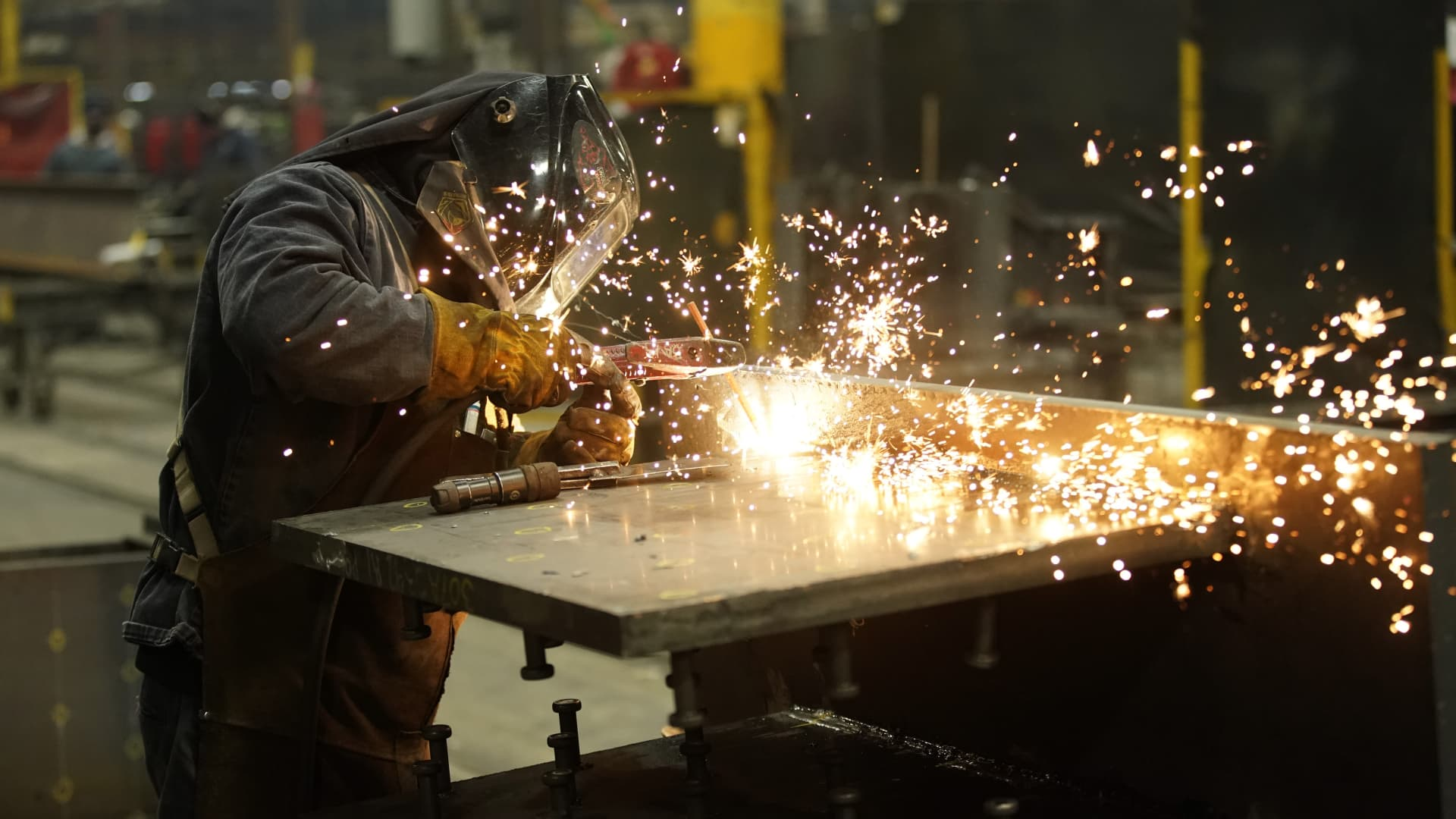 A worker welds a structural steel beam during production at the SME Steel Contractors facility in West Jordan, Utah, on Feb. 1, 2021.