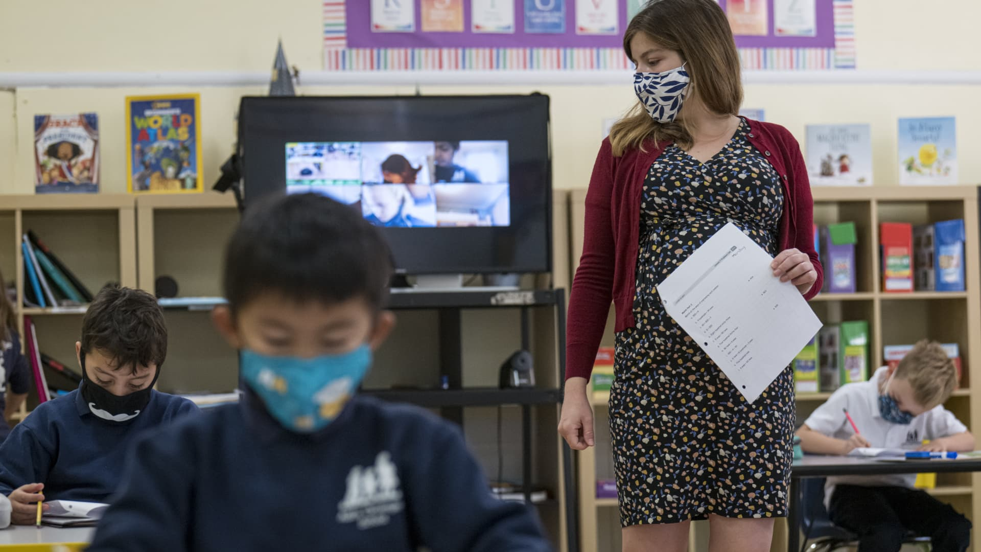A teacher wearing a protective mask walks around the classroom during a lesson at an elementary school in San Francisco, California, U.S., on Monday, Oct. 5, 2020.