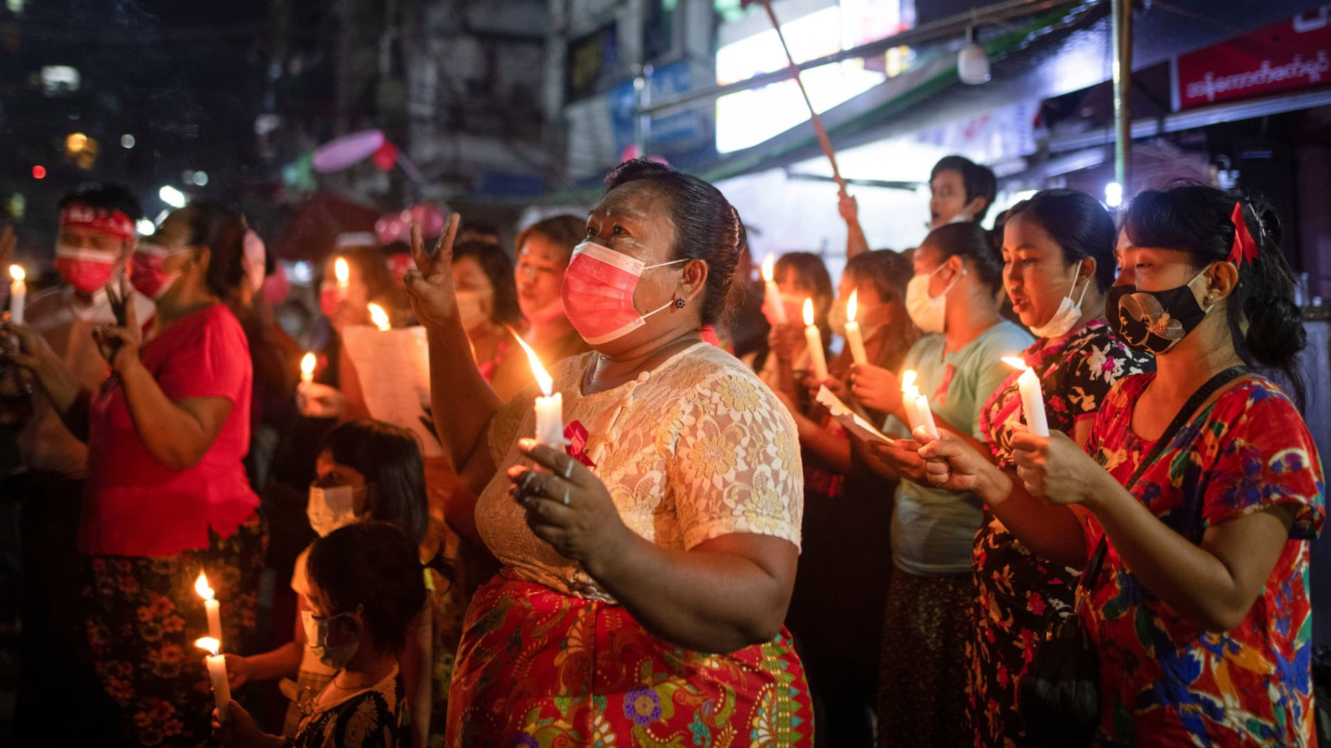Women wearing red ribbons hold candles during a night protest against the military coup in Yangon, Myanmar February 5, 2021.
