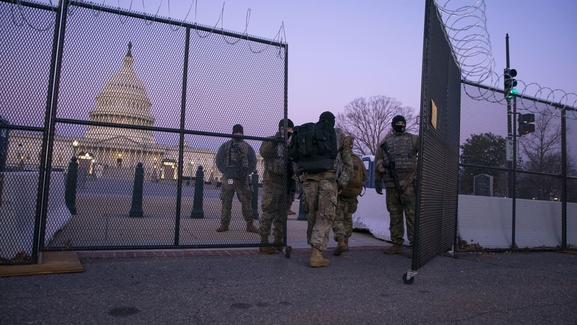 Members of the National Guard enter a gate of barbed wire fencing on U.S. Capitol grounds at sunrise on February 8, 2021 in Washington, DC. The Senate is scheduled to begin the second impeachment trial of former U.S. President Donald J. Trump on February 9.