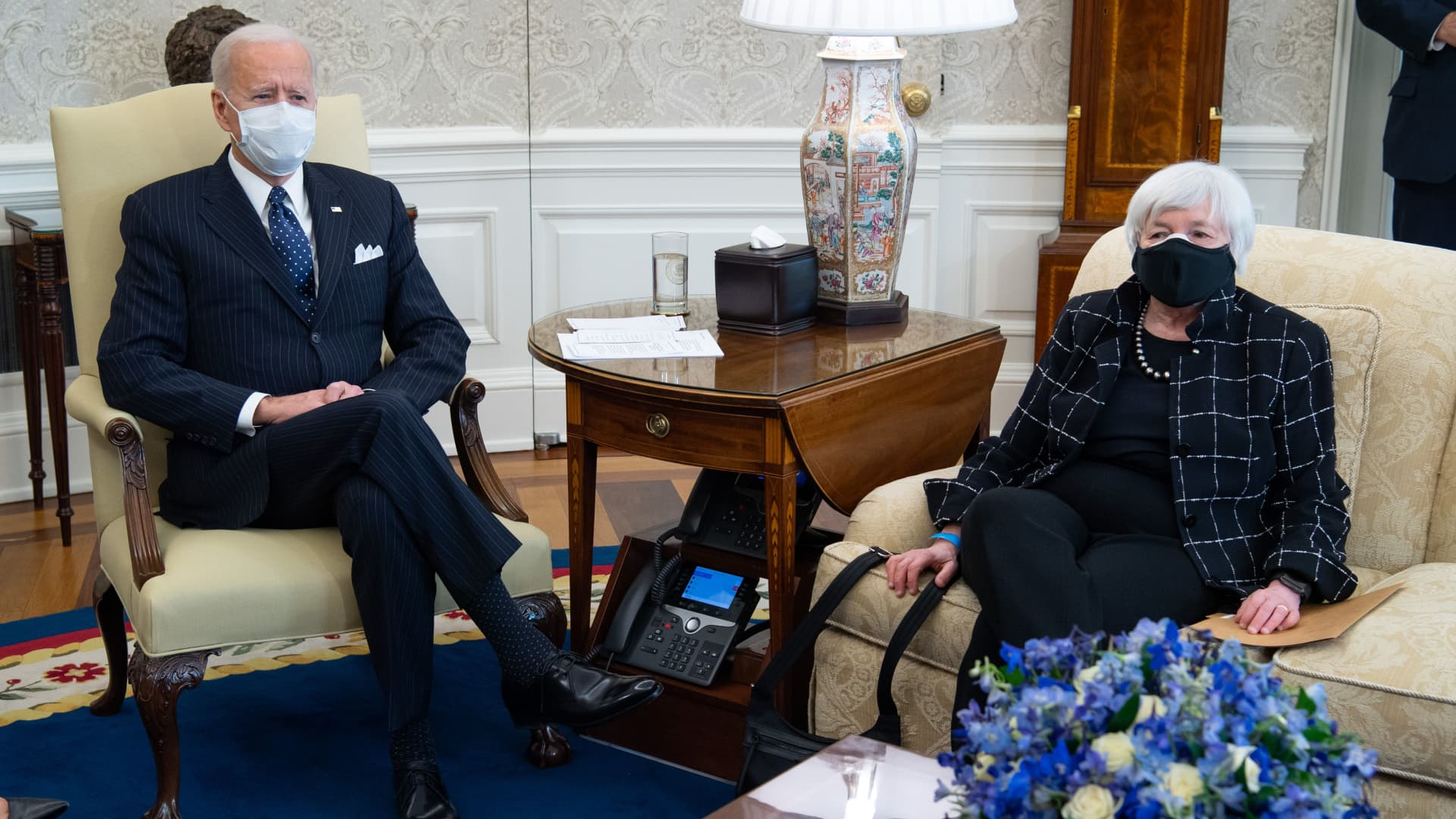 President Joe Biden sits alongside US Treasury Secretary Janet Yellen (R) as he holds a meeting with business leaders about a Covid relief bill in the Oval Office of the White House in Washington, DC, February 9, 2021.