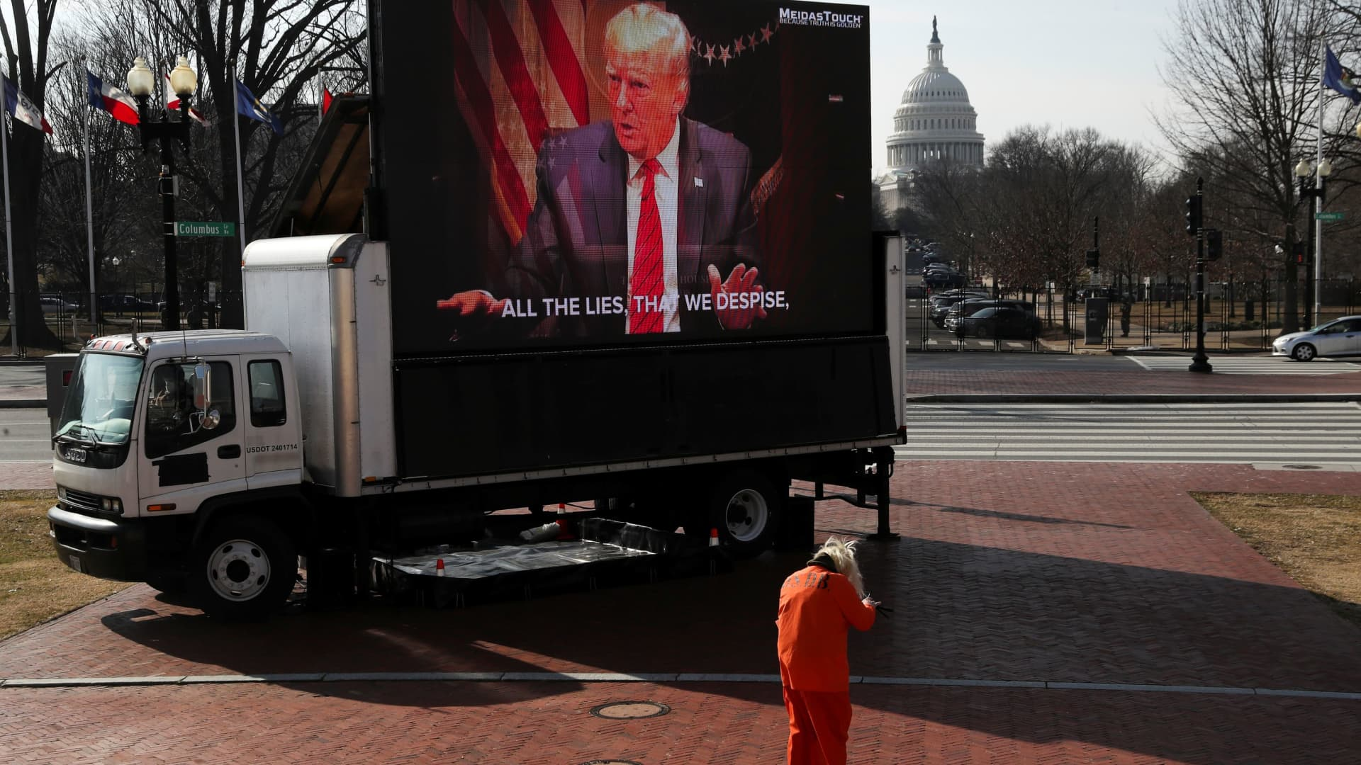 A protester is seen near a giant screen as it airs advertisements in support of convicting former U.S. President Donald Trump as the second day of his impeachment trial begins in Washington, February 10, 2021.
