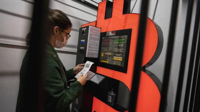 Seorang wanita menggunakan mesin ATM Bitcoin yang ditempatkan di dalam kandang pengaman pada tanggal 29 Januari 2021 di Barcelona, Spanyol.