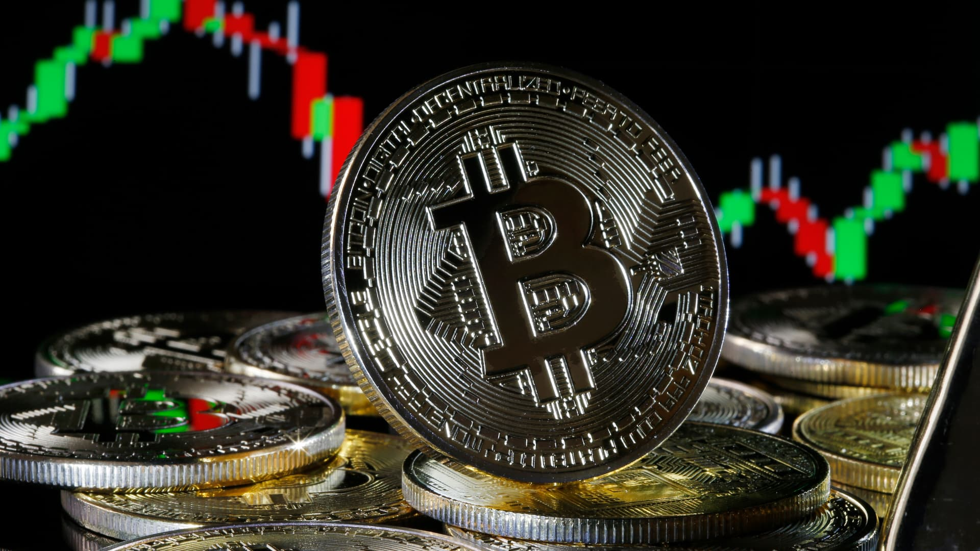 In this photo illustration, a visual representation of the digital Cryptocurrency, Bitcoin is on display in front of the Bitcoin course's graph on February 09, 2021 in Paris, France.
