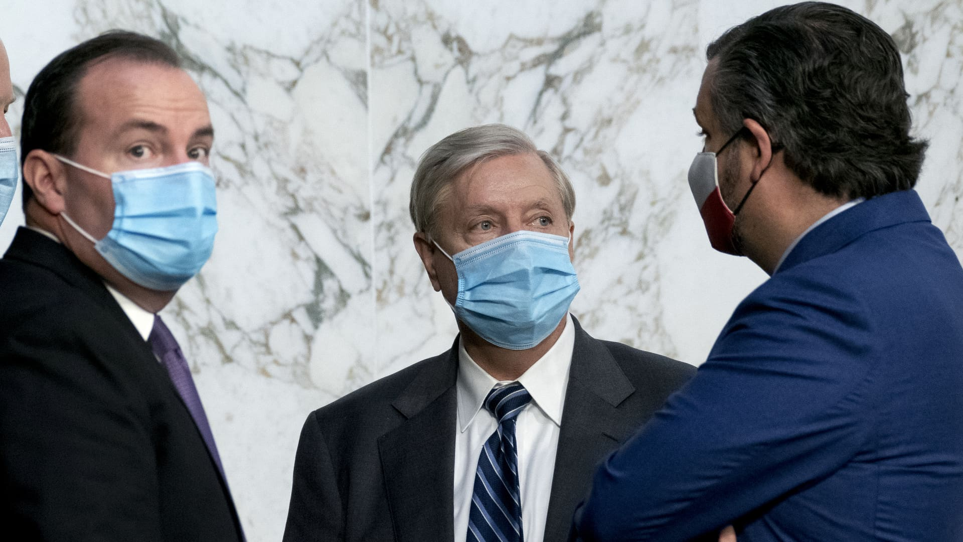 From left, Senator Mike Lee, a Republican from Utah, Senator Lindsey Graham, a Republican from South Carolina and chairman of the Senate Judiciary Committee, and Senator Ted Cruz, a Republican from Texas, wear protective masks while talking during a break of a confirmation hearing in Washington, D.C., U.S., on Wednesday, Oct. 14, 2020.