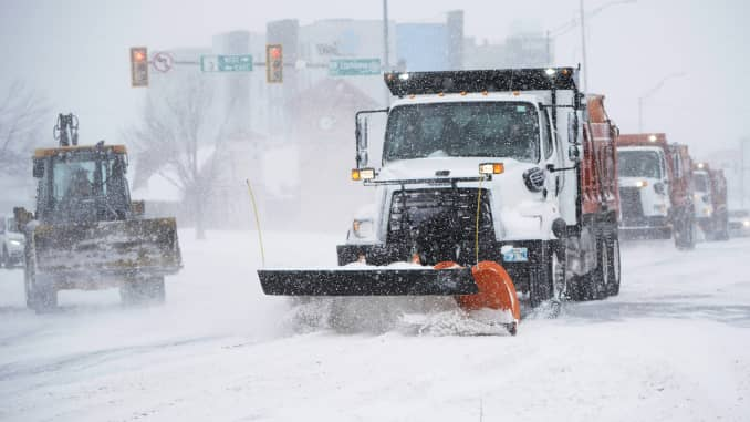 Vehicles work to clear an intersection during a winter storm Sunday, Feb. 14, 2021, in Oklahoma City.