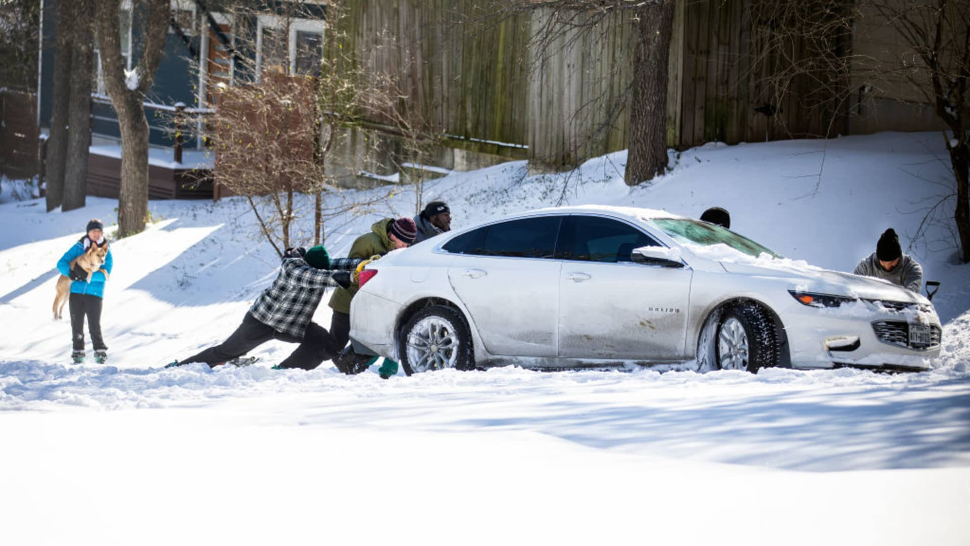 East Austin residents push a car out of the snow on February 15, 2021 in Austin, Texas.