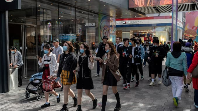 "People walk outside a shopping mall complex during the country's national ""Golden Week"" holiday in Beijing on October 2, 2020. (Photo by NICOLAS ASFOURI / AFP) (Photo by NICOLAS ASFOURI/AFP via Getty Images)"