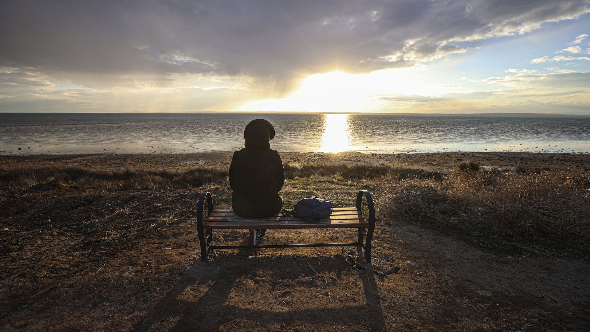 A person enjoys the view while sitting on a bench at the Lake Tuz during sunset in Ankara, Turkey on February 12, 2021.