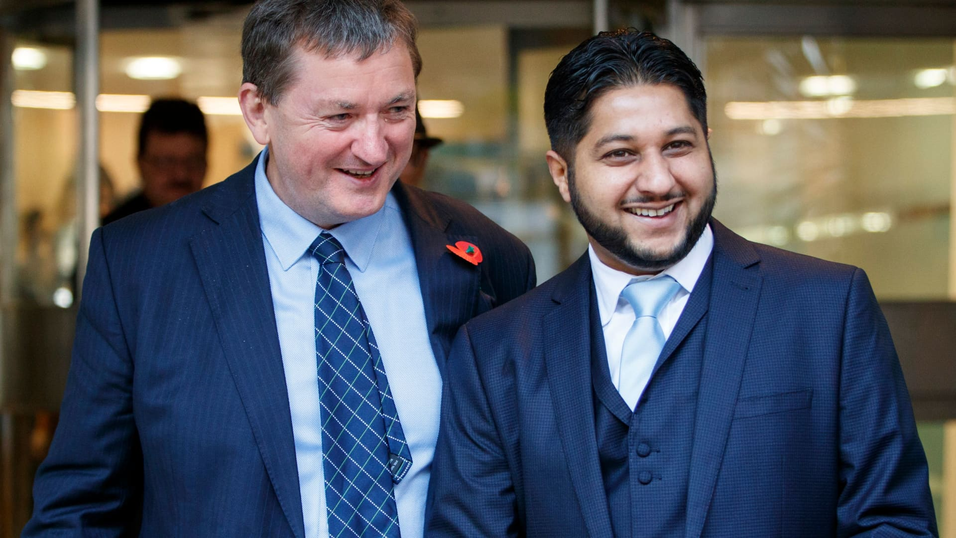 Former Uber drivers James Farrar (L) and Yaseen Aslam react as they leave the Employment Appeals Tribunal in central London on November 10, 2017.