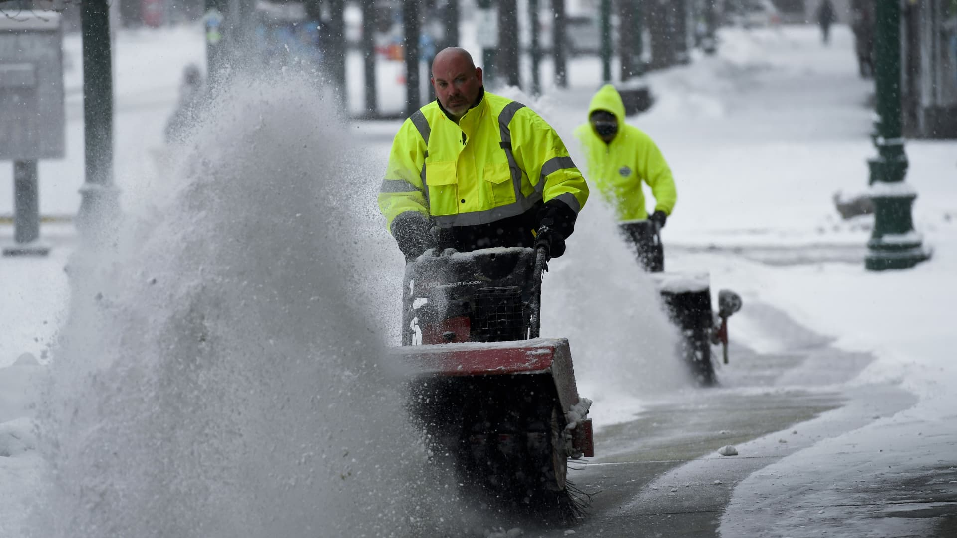 Employees with the Reading Public Works department clear snow from a sidewalk on the 400 block of Penn Street using snow blowers.