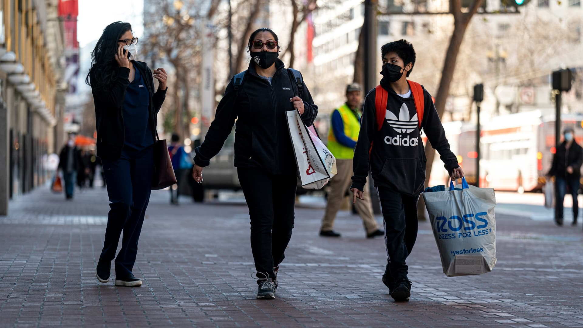 Pedestrians wearing protective masks carry shopping bags in San Francisco, California, on Wednesday, Feb. 17, 2021.