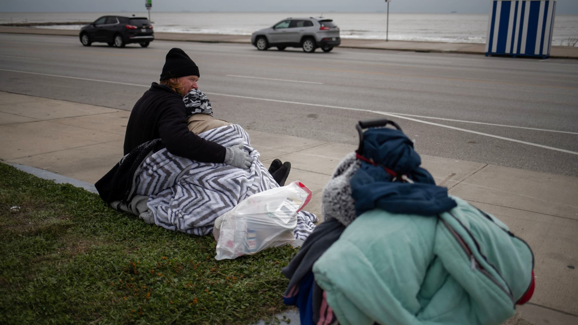 Couple Renne Alva, 37, and Travis Wasicek, 43, sit amongst their belongings along Seawall Boulevard as they embrace to keep each other warm after record-breaking winter temperatures in Galveston, Texas, February 18, 2021. The couple said they became homeless last year after losing their jobs due to the economic fallout from the coronavirus (COVID-19) global pandemic.