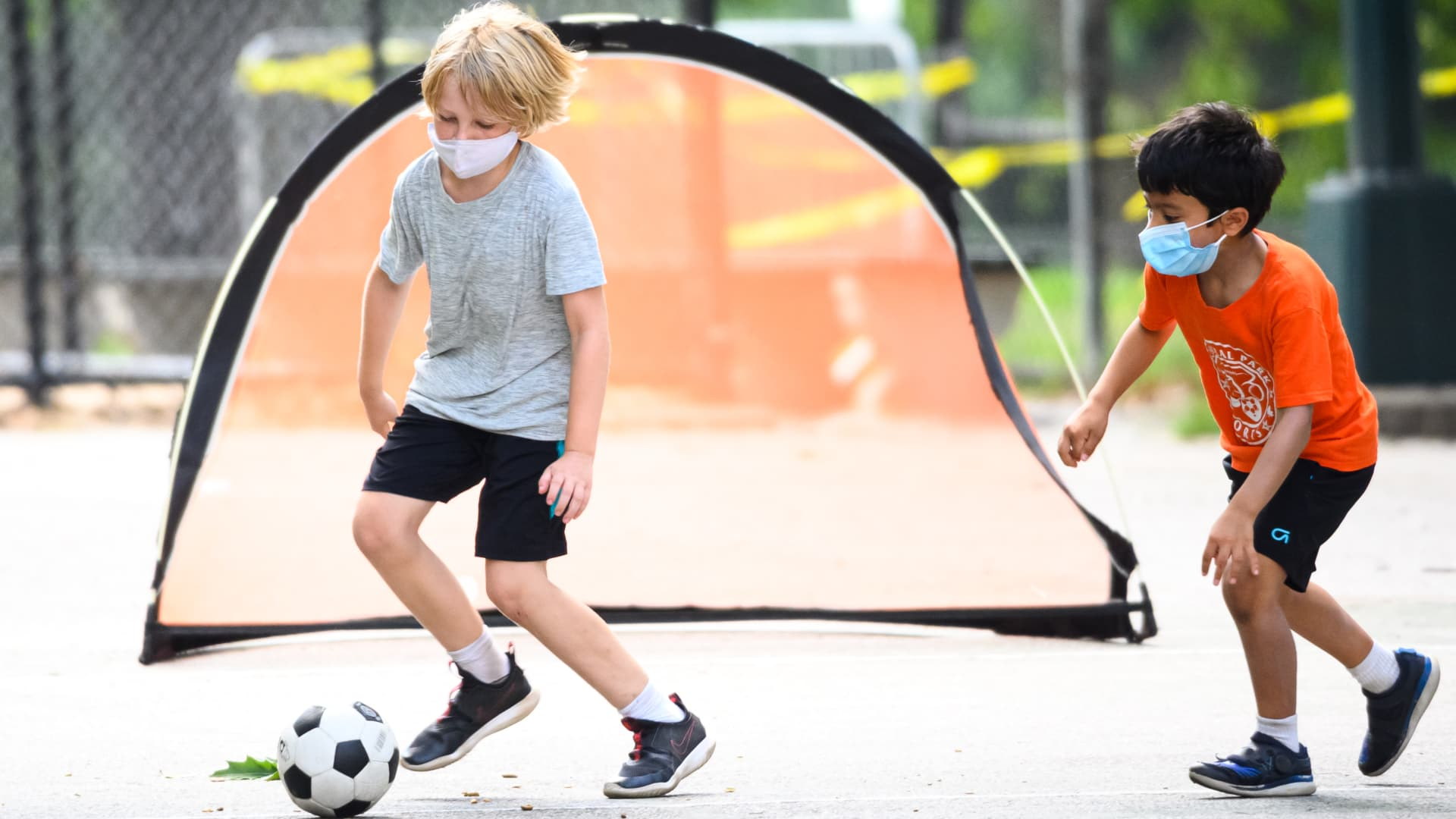 Kids wear face masks while playing soccer.