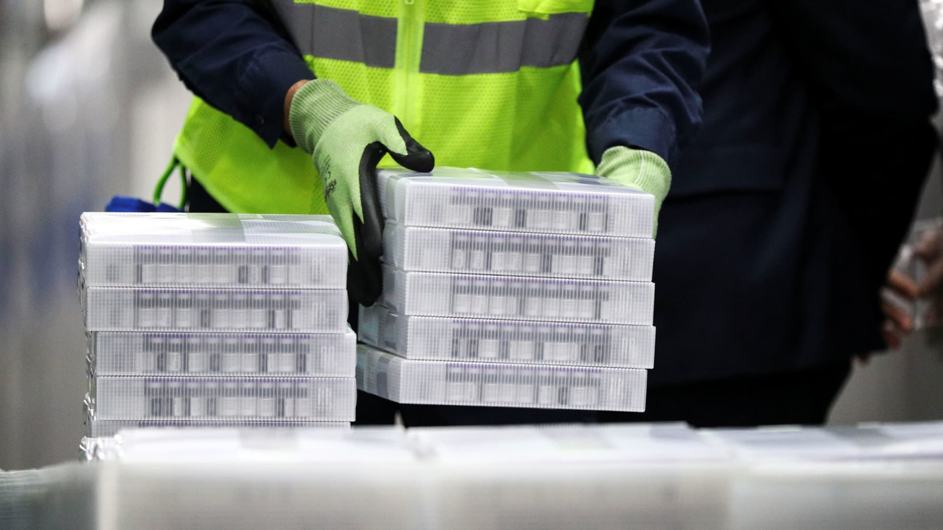 Pfizer employees handle containers of vaccine as U.S. President Joe Biden tours a Pfizer manufacturing plant producing the coronavirus disease (COVID-19) vaccine in Kalamazoo, Michigan, U.S., February 19, 2021.